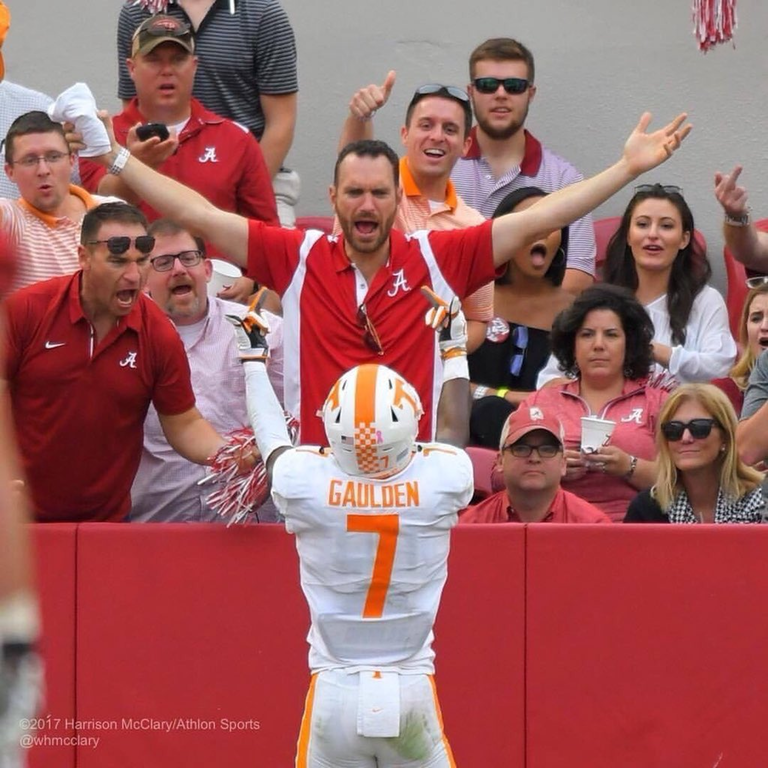 Football player flipping off the crowd after scoring a touchdown.