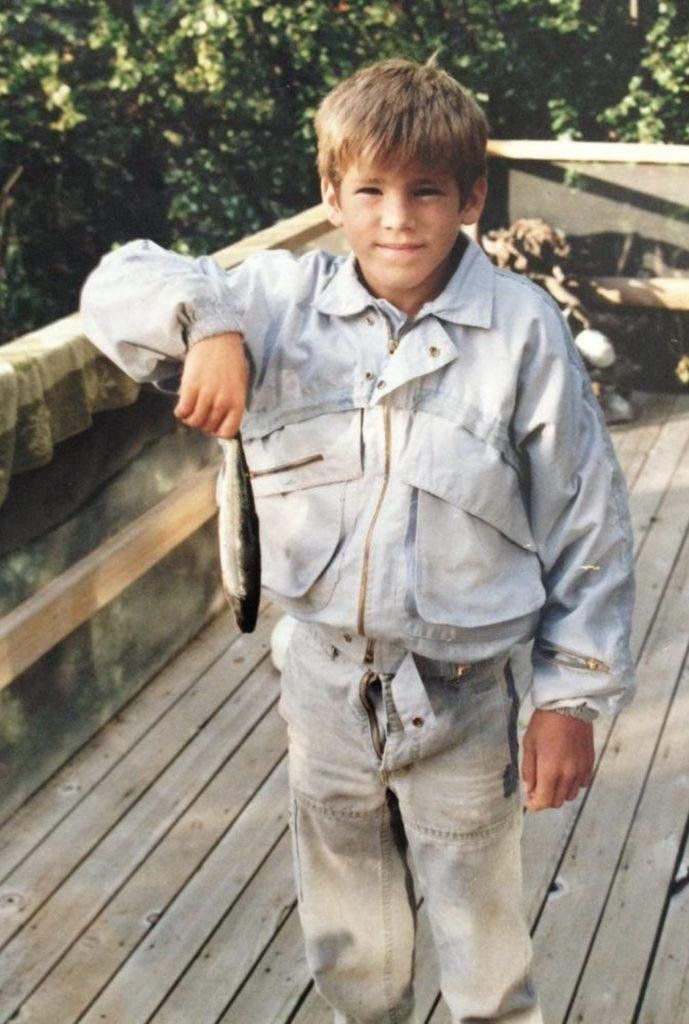 Before he was Deadpool. Ryan Reynolds in 1983. Double denim, holding a dead fish, with his fly open.