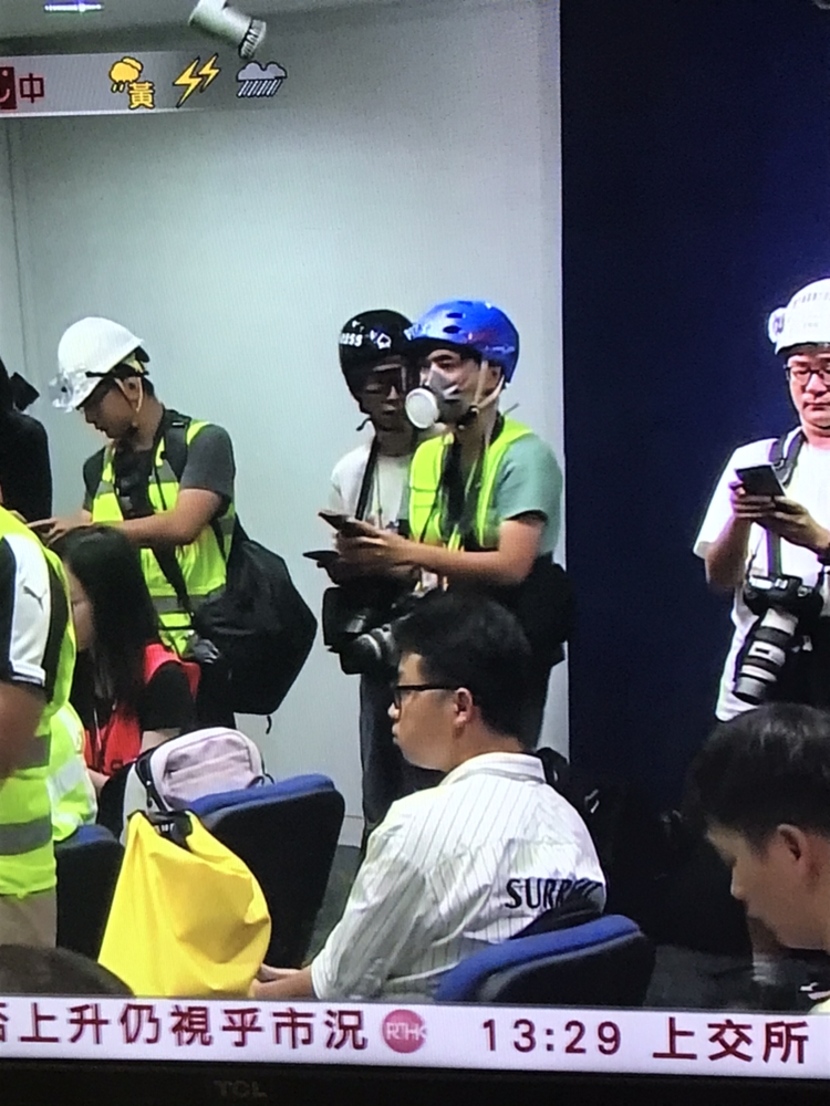 Journalists wearing helmets and gas masks while attending Hong Kong Police Force's press conference