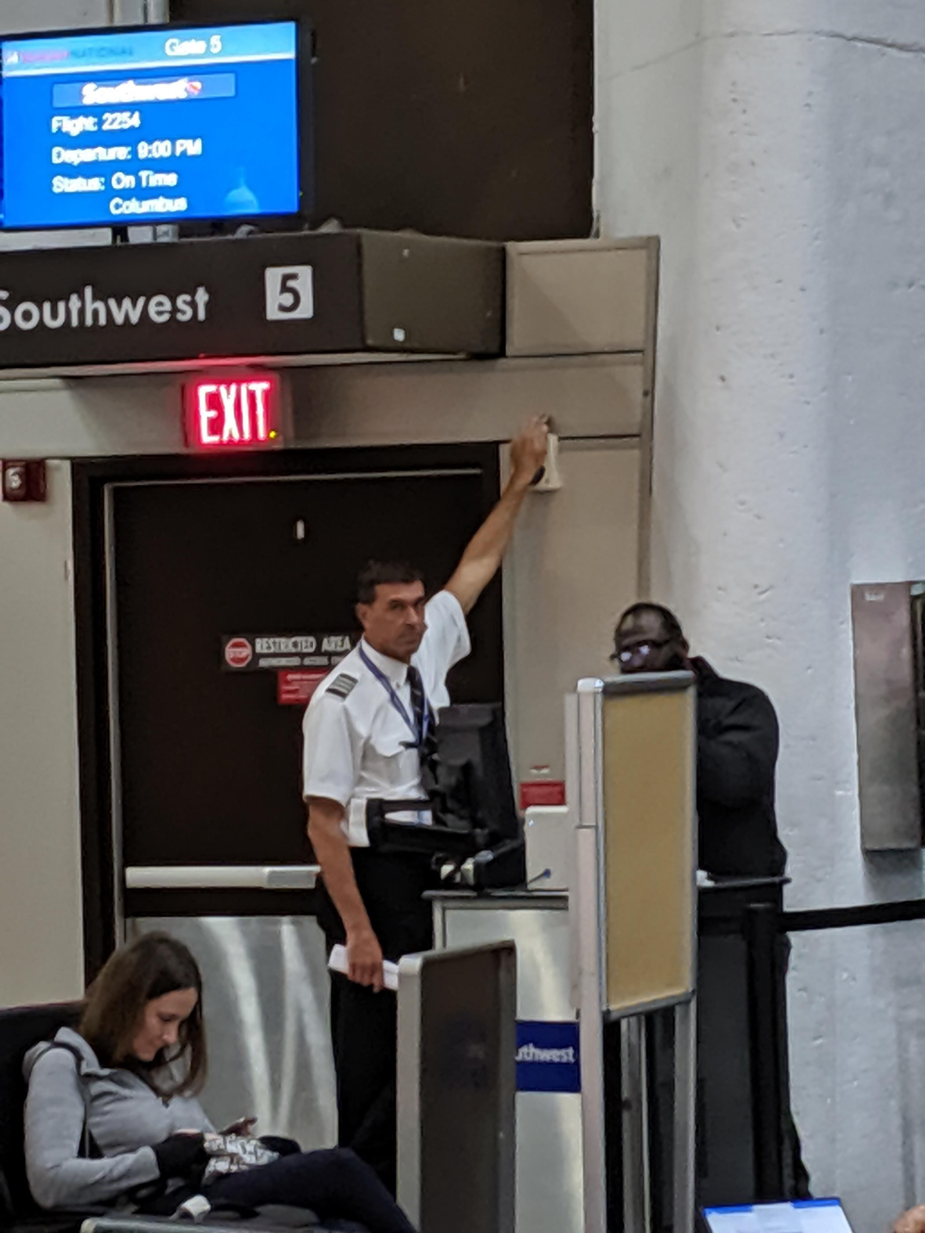 Pilot set off a door alarm, but security needs to come check it out. He's been covering the siren for 5 minutes.
