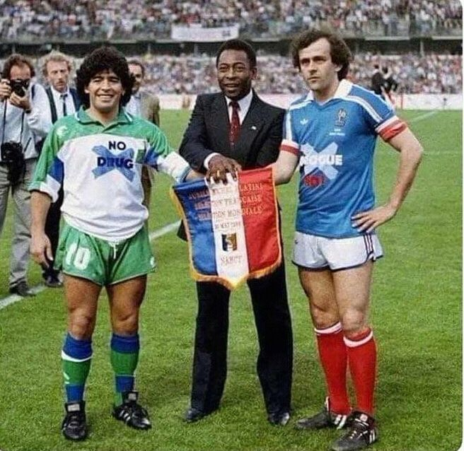 "It is year 1986. Maradona is wearing ""no drugs"" shirt. Platini is wearing ""no corruption"". Time flies."