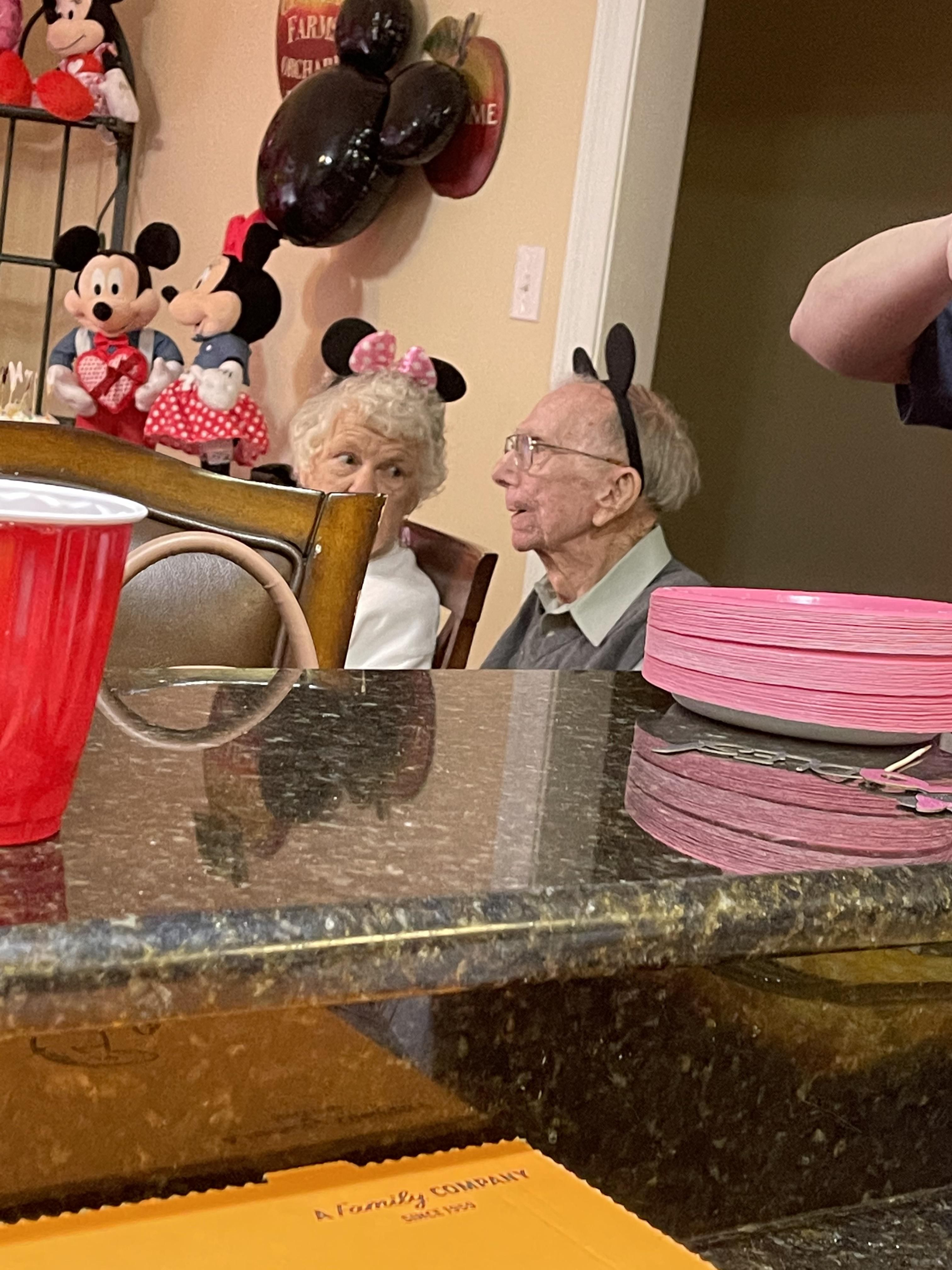 These two old people wearing mouse ears at a two year olds b day party
