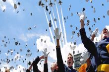 Horrified graduates flee as planes attack crowds with hats.